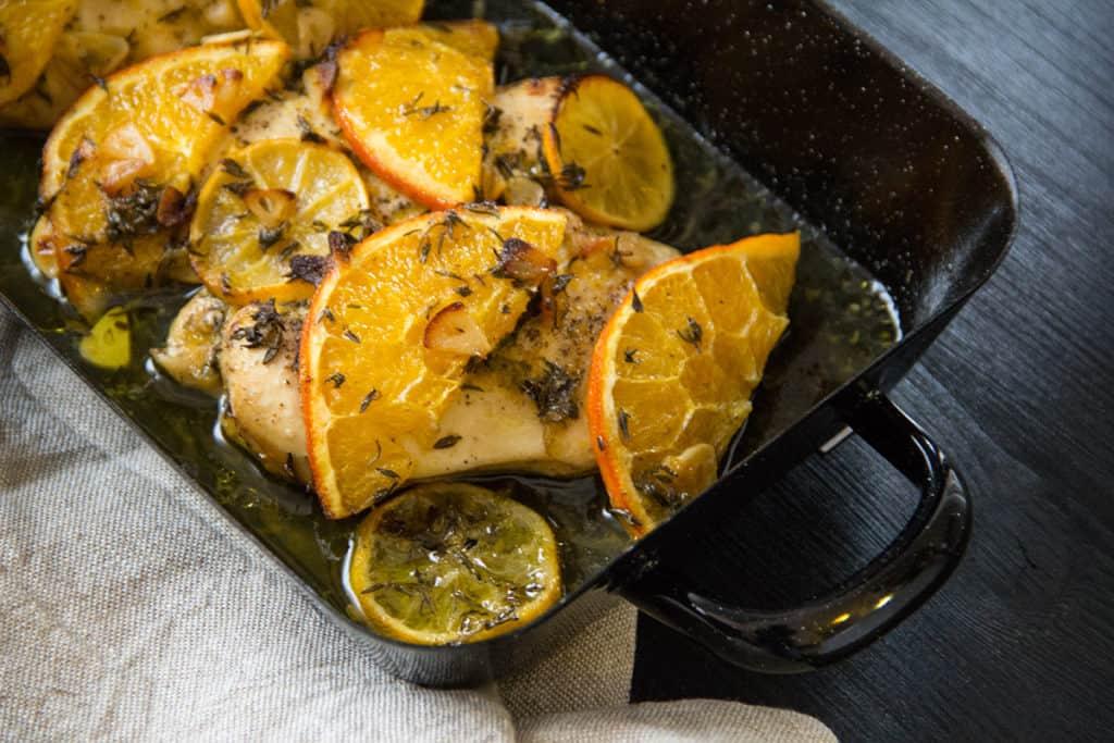 Huhn mit Orangen- und Zitronenscheiben, gewürzt mit Kräutern, Knoblauch und Olivenöl.