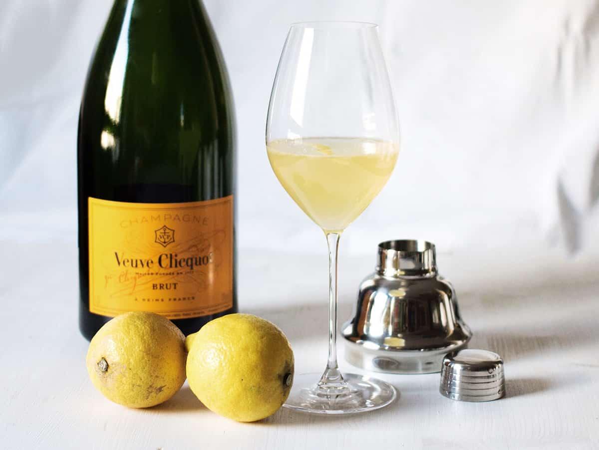 French 75 mit Champagnerflasche und Zitronen